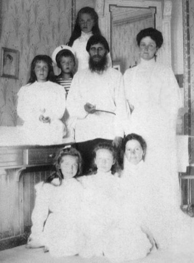Black and white photograph of Tsarina Alexandra with her children, Rasputin and the governess. All are wearing white garments. Immorality psyop.