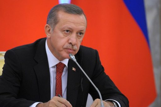 Colored photograph of Prime Minister Erdogan, seated in front of microphone.  Red background. He is wearing  a dark suit, with red tie. Future Assyrian - Isaiah 10.