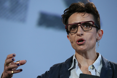 Colored photograph of woman with short, black hair and glasses giving a speech with right hand raised. One flesh.