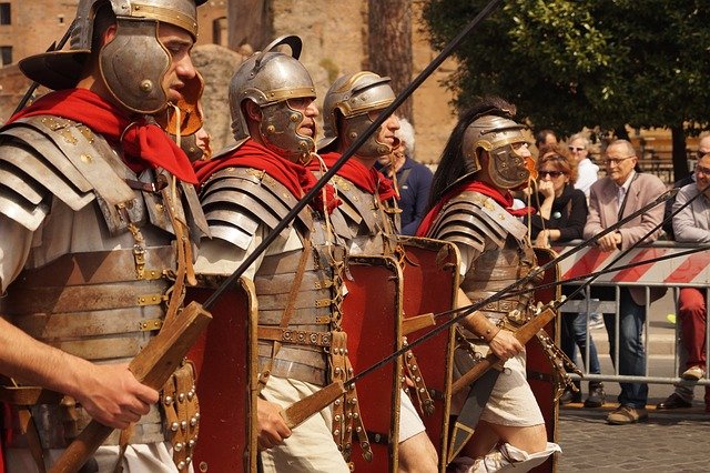 Colored photograph of men dressed as Roman soldiers parading in front of the public. Brown building in background. When in Rome?