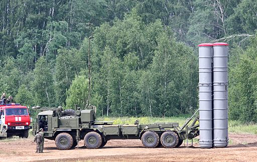 Colored picture of 8-wheeled missile carrier with missile carrying tubes positioned vertically at rear. Green trees and green and red truck in background. When in Rome?