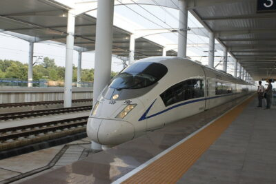 Colored photograph of a sleek, white Chinese train with tinted windows at a platform. Mark from the East.