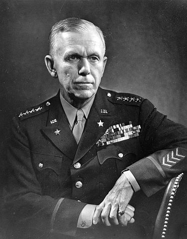 Black and white photograph of a United States general in uniform, seated and having serious expression on his face. Mark from the East.
