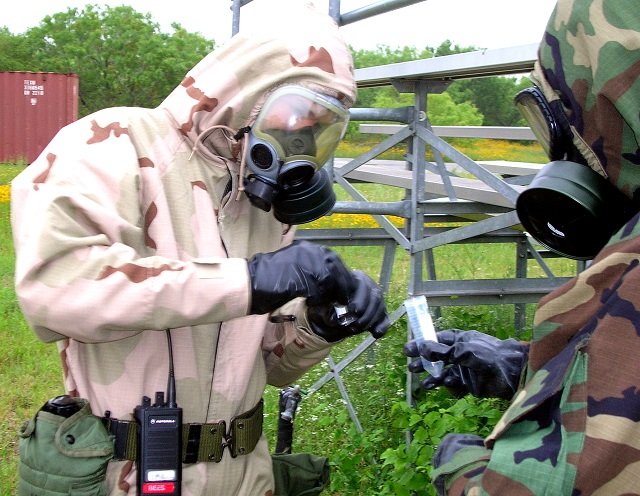 Colored photograph of 2 soldiers, one wearing light coloured camouflage suit and the other in a dark green camouflage suit. Gloved hands holding a cylindrcal metal object. Prophetic pestilence