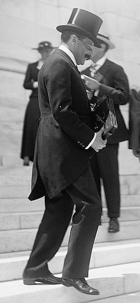 Black and white photograph of a man in top hat and tails on tall, stone steps with a lady and man in background. Blame Game.