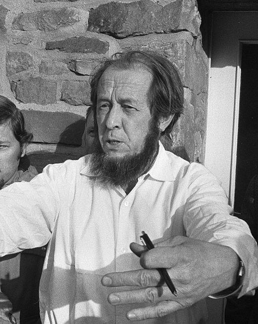 Black and white photograph of Aleksandr Solzhenitsyn,  dark hair and beard ,  white shirt. Meet Gog?