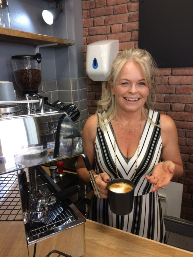 Staff member holding a cup of coffee made on a barista machine