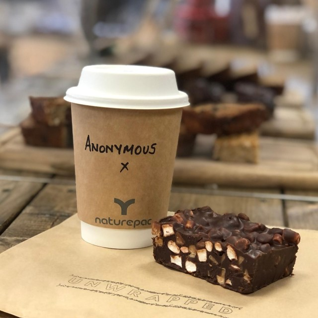 "photo of a coffee cup and rocky road on an Unwrapped napkin with the words ""Anonymous"" written on the cup"