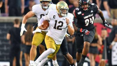 Photo of Watch: Notre Dame Quarterback Ian Book's Pass Lands Right in the Face of a Louisville Cheerleader
