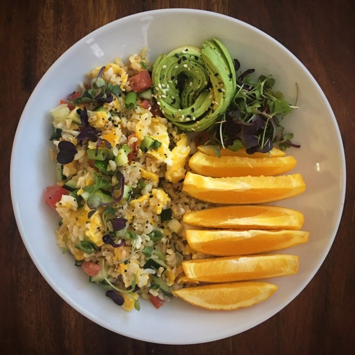 Scrambled Eggs with Brown Rice Salad (Cucumber, Zucchini, Tomatoes, Green Onions, Cilantro), Avocado, Microgreens, and an Orange