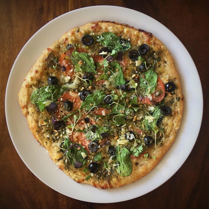 Pizza with Spinach, Tomatoes, Olives, Microgreens, Cheese, and Vegetarian Bacon Bits