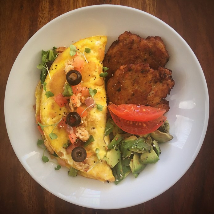 Crab Cake Omelette with Zucchini Pancakes, Spinach, Tomato, Olives, and Avocado