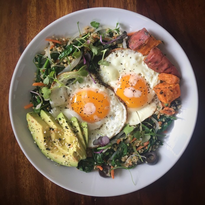 Breakfast Food Nest of Eggs and Avocado, Spinach, Tabouleh Salad, Carrots, Onion, Olives, and Microgreens, with Sweet Potatoes