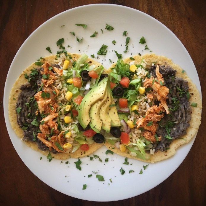 Una Fiesta de Tacos con Pollo, with Refried Black Beans, Brown Rice, Corn, Lettuce, Olives, Onions, Tomatoes, Avocado, and Cilantro