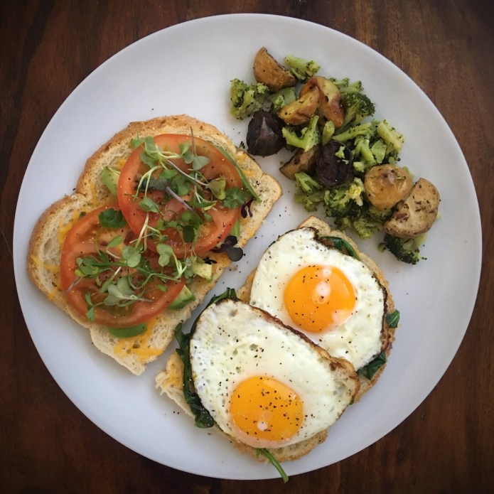 Fried Egg Sandwich on Sourdough, with Spinach, cheese, Tomato, Avocado, and Microgreens, with a Side of Broccoli and Potatoes
