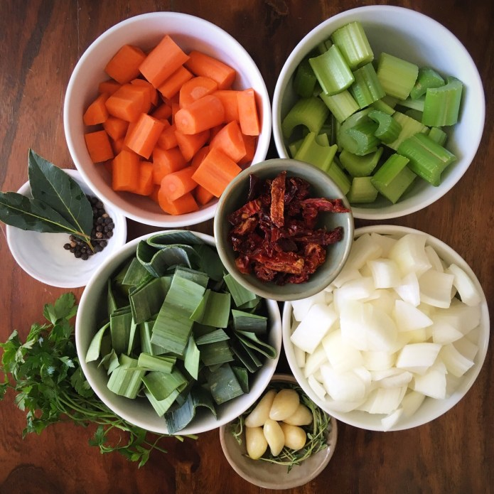 Mise En Place of Carrots, Celery, Sun Dried Tomatoes, Onions, Leeks, Bay Leaves, Garlic, Thyme, Peppercorns, and Parsley