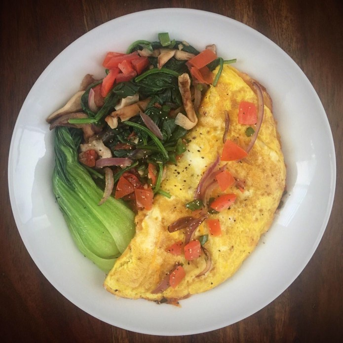 Breakfast Roundup: Cheesy Omelette, Topped with Onions, and Tomatoes, With a Side of Veggies: Spinach, Mushrooms, Onions, and Bok Choy