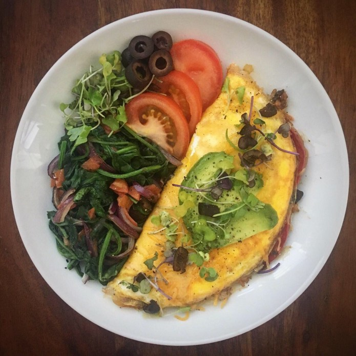 Fajita Omelette with Beans, Cheese, Corn, Peppers, and Onions, Topped with Microgreens, and Avocado, Side of Spinach, Tomatoes, Olives and Microgreens