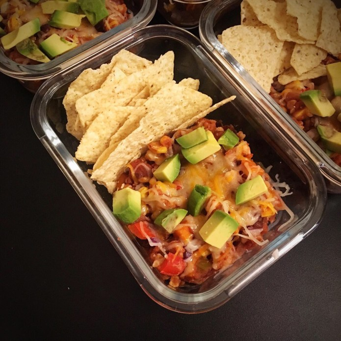 Veggie Chili topped with Cheese, Red Onion, and Avocado, with a Side of Corn Chips