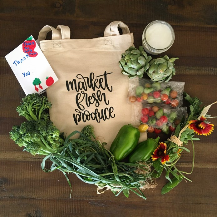 Market Fresh Produce Linen Bag Surrounded by Fruits and Veggies: Broccoli, Green Onion, Green Bell peppers, Tomatoes, and Artichokes, with Wildflowers, Coconut Oil Sugar Scrub, and A Thank You Card