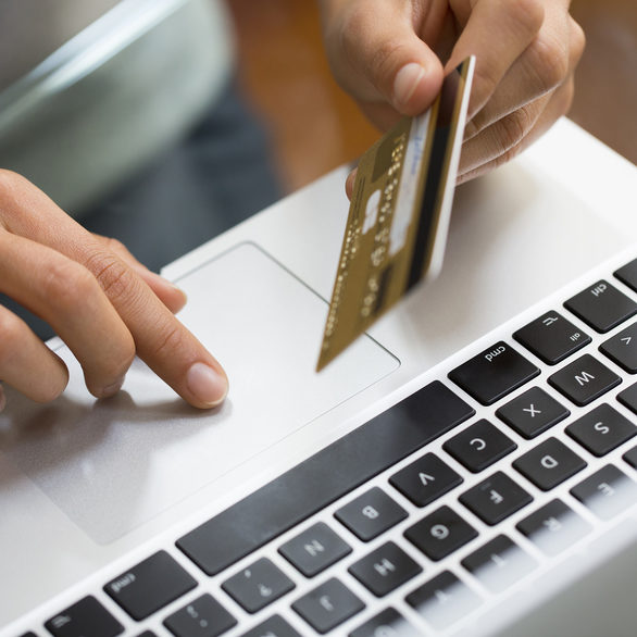 Close-up hand woman using laptop and credit card, online shopping