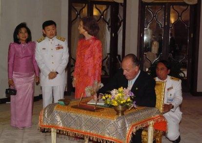 El Rey firma en el libro de honor en Villa Norasingh, en presencia de la Reina y el Primer Ministro tailandés y su esposa