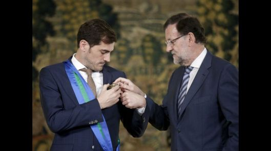 Spanish goalkeeper Iker Casillas and Spain's Prime Minister Mariano Rajoy attempt to hang the Grand Cross of the Royal Order of Sporting Merit on Casillas' jacket at the Moncloa Palace in Madrid