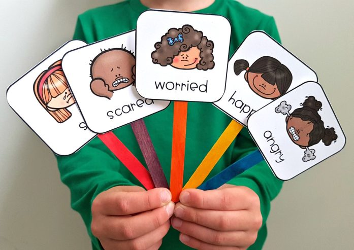 teaching empathy skills - feeling pictures on popsicle sticks held up by child
