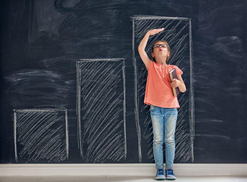 girl measuring her height against the blackboard