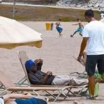 Un guardia urbano de paisano (de blanco) interpela a un latero que se hace pasar por bañista, ayer en la playa del Somorrostro.