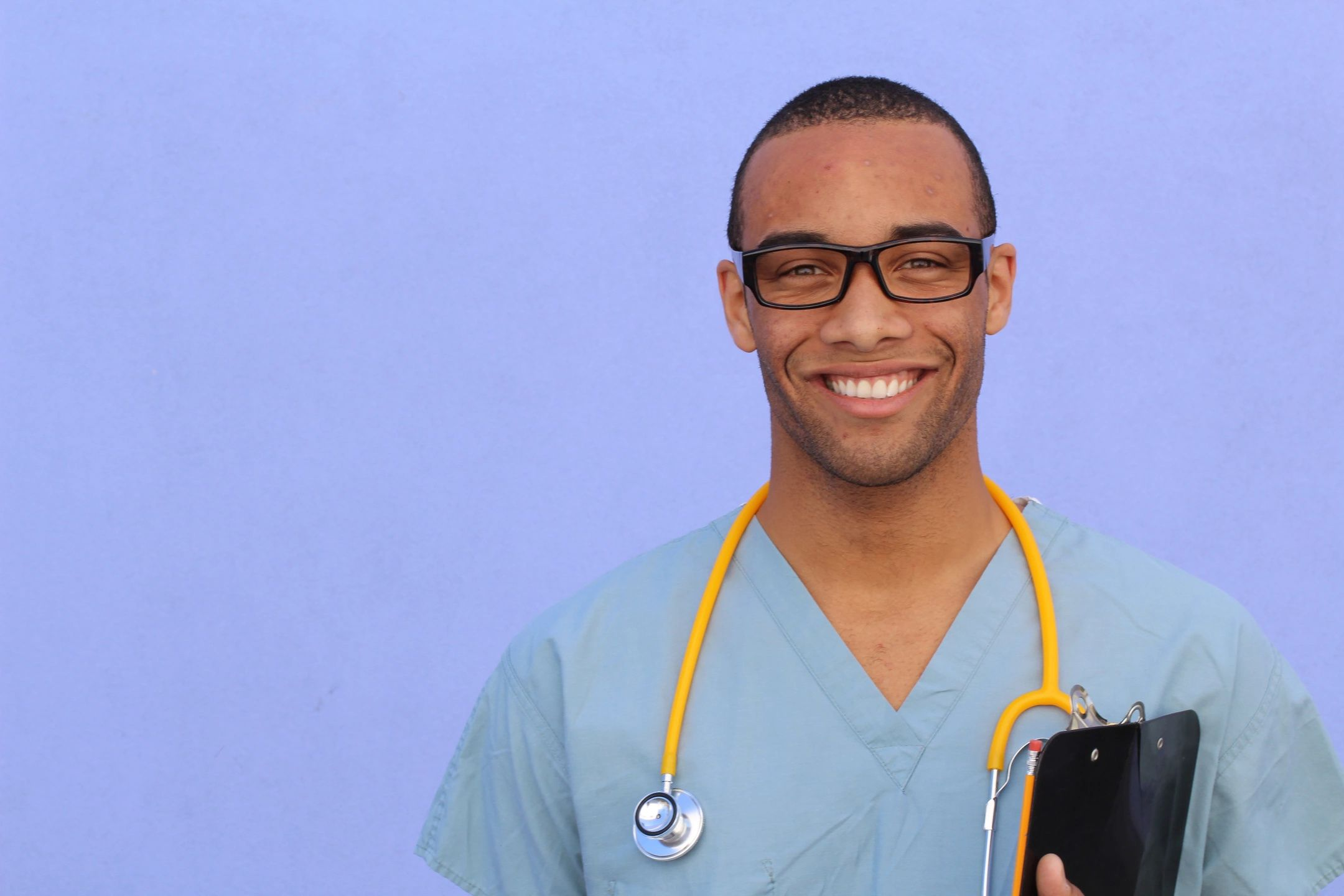 Healthcare worker wearing blue scrubs, glasses and a yellow stethoscope holding a clipboard and smiling at the camera