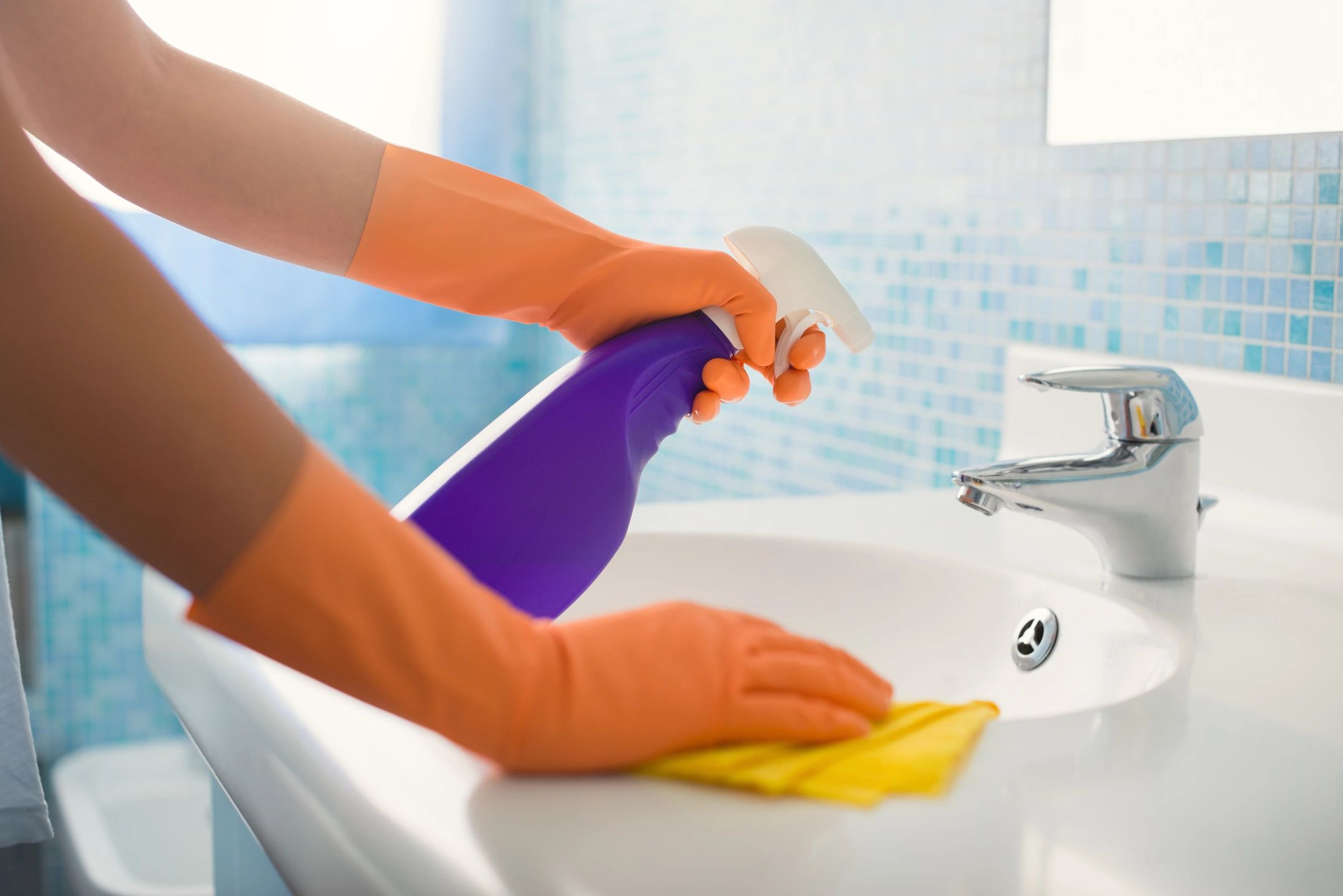 Person wearing rubber gloves cleans a sink with a spray bottle and a cloth