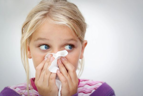 Girl holding a tissue to her nose