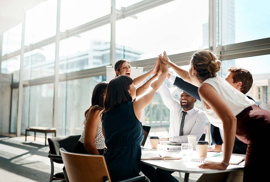 Happy team of property managers high-fiving in office