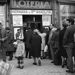"""""""Haciendo cola para comprar un décimo del sorteo de la Navidad. Administración de lotería Doña Manolita, Puerta del Sol, Madrid. 1974"""" - Benito Román - 221214"""