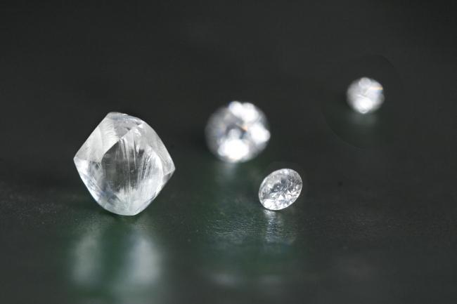 手前(左)カット・研磨前の天然ダイヤモンドと(右)グランバーガープレシジョンカット(R)完成品メレダイヤモンド(従来の58面カット)