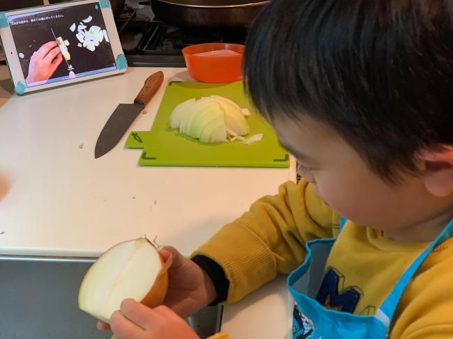 FamCookの子手伝い機能で玉ねぎの皮をむく男の子。パパの料理塾で学んだ料理を親子で復習中。
