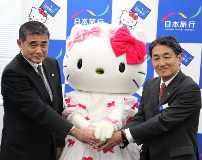 写真左が、サンリオ 専務取締役 福嶋一芳、真ん中がハローキティ、右が日本旅行 代表取締役社長 堀坂明弘