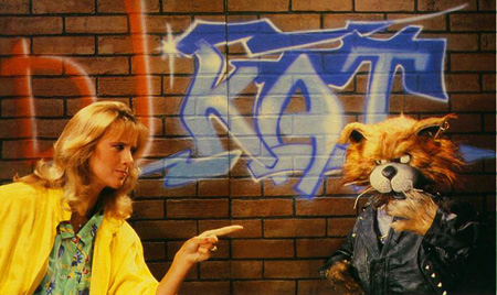 DJ Kat show. Denk aan sekskitten, en ze heeft een gele jas aan zoals de yellow brick road van de Wizard of Oz