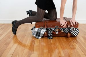 business-traveller-woman-packing-clothes-into-overstuffed-suitcase