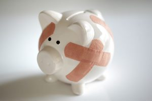 relationship-to-money-piggybank-with-plasters