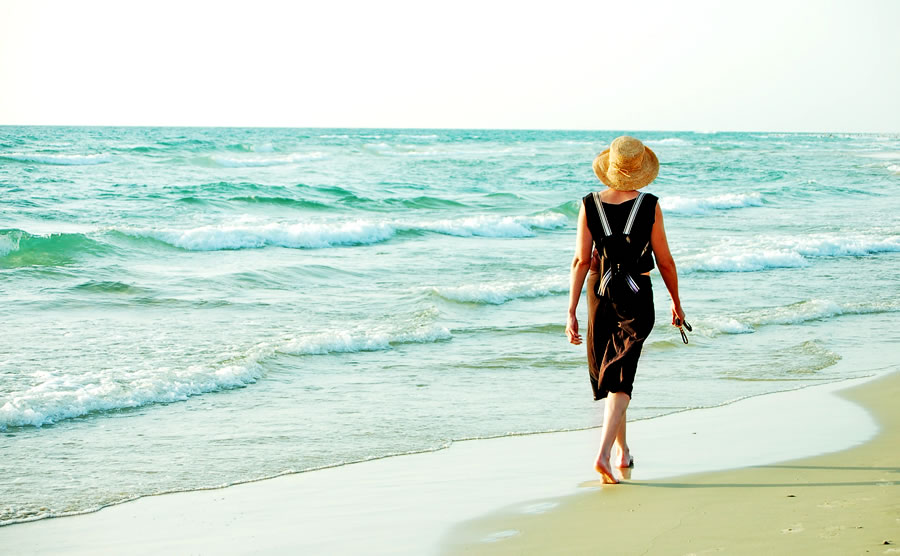 expat-woman-walking-on-the-beach