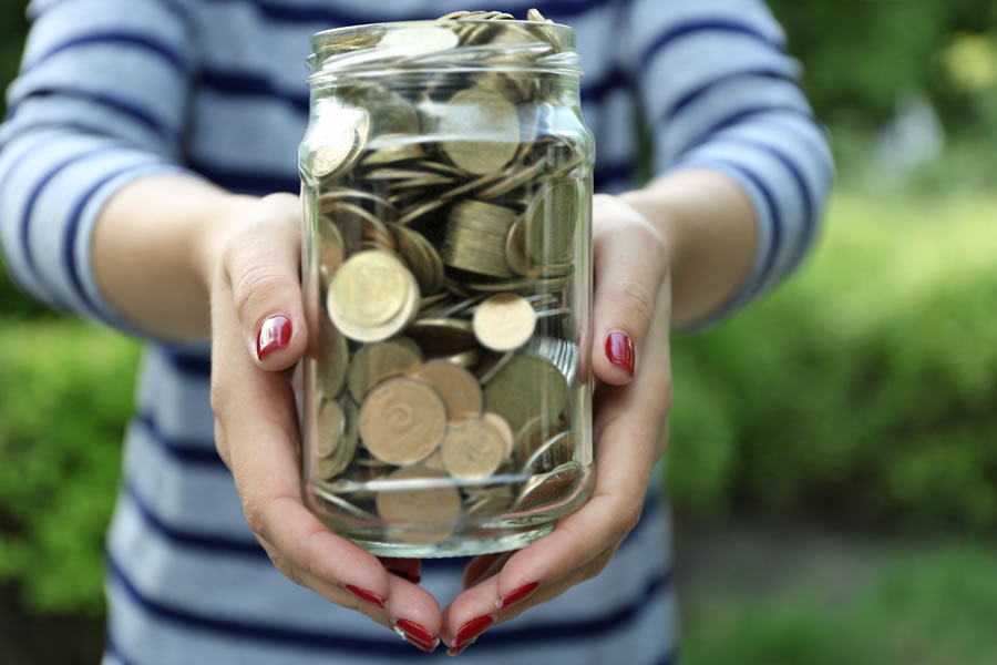 money-stories-woman-holding-money-jar-with-coins-outdoors