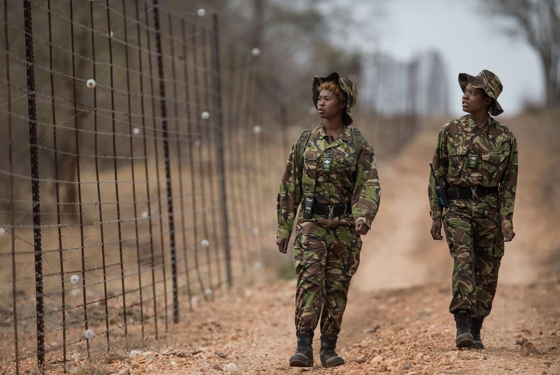 Black Mambas Women Anti-poaching Unit - two-women-walking-along-fence