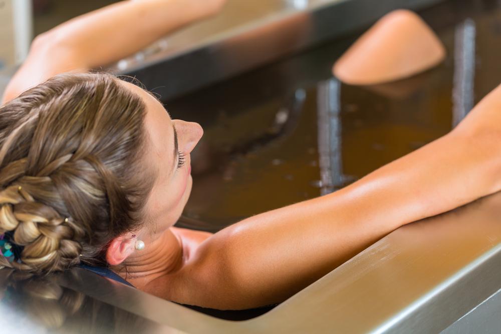 Girlfriend Getaway - woman enjoying mud bath alternative therapy
