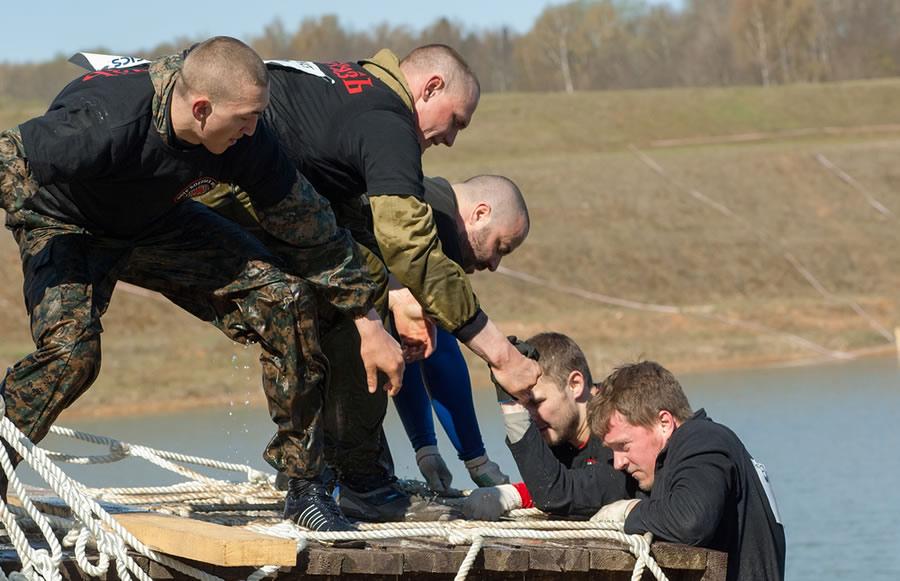 Grit - men-helping-other-men-climb-wall