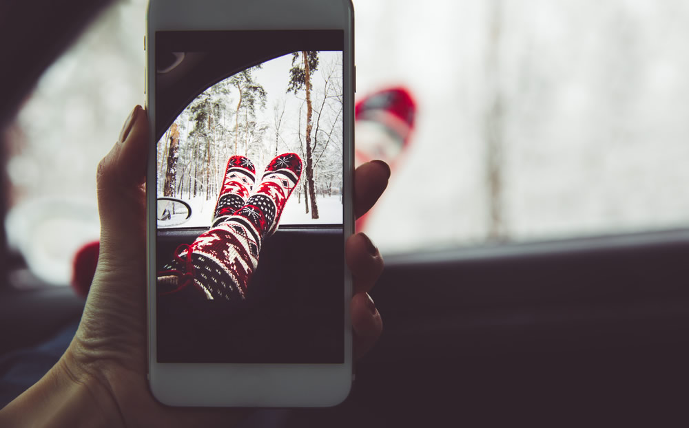Holiday Spending - woman taking selfie of feet in christmas socks