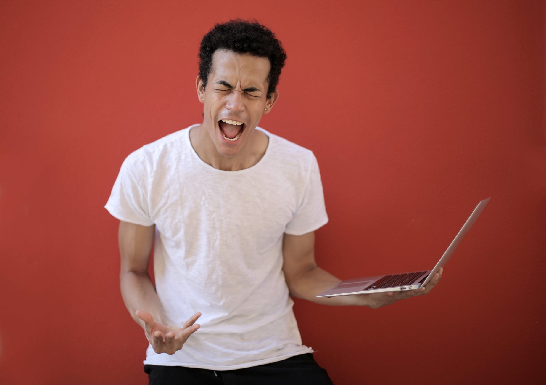 young ethnic male with laptop screaming