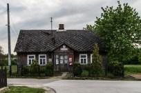 drewniany wiejski budynek z czerwonymi tablicami informacyjnymi