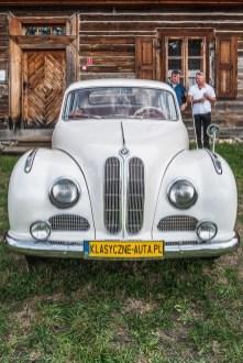 duży biały samochód przed drewnianym budynkiem